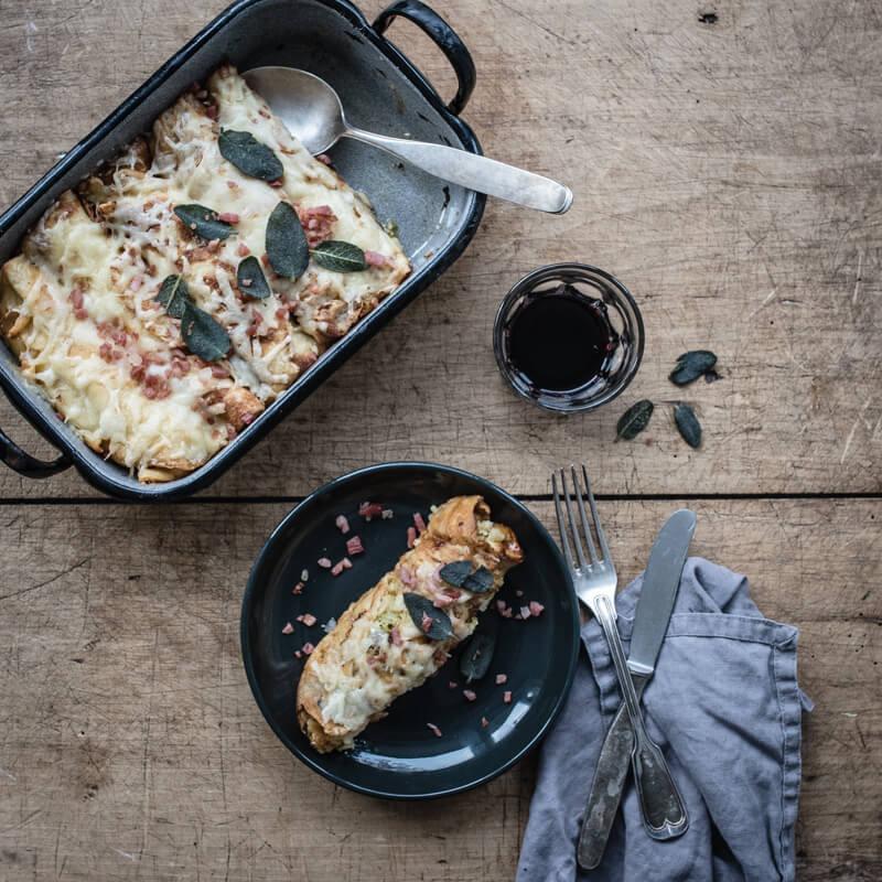 Köstliche Speckbutter Crespelle, gefüllt mit Wirsing, Speck, Apfel und mit Bergkäse im Ofen gratiniert
